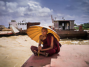 12 JUNE 2013 - YANGON, MYANMAR: Buddhist monks sit on a pier on the Irrawaddy River in Yangon, Myanmar.          PHOTO BY JACK KURTZ