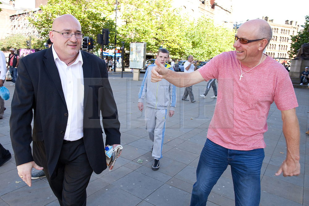 © Licensed to London News Pictures .  08/09/2012 . Manchester, UK . Domenyk Noonan (left) , recently released from prison , walks through Manchester 's Piccadilly Gardens , accompanied by his Nephew , Kieran Noonan (centre in grey tracksuit) . A stranger shakes his hand and give him a thumbs up in the street . The area was the scene of looting and rioting on 9th August 2011 , during which Noonan was arrested . Noonan has announced he plans to sue the police over the  arrest . Under the terms of a previous early release , the arrest lead to him being recalled to prison . Photo credit : Joel Goodman/LNP