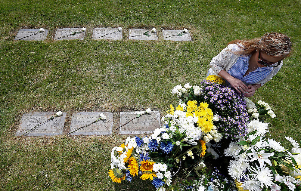 """Suzy Matusiewicz sits beside the flowers covering the grave of an abandoned newborn baby boy during a burial service at All Saints Cemetery in Des Plaines, Illinois, United States, June 19, 2015. More than a year after he was found dead in a plastic shopping bag on a Chicago sidewalk, the baby boy was buried by a non-profit group """"Rest in His Arms"""" after being abandoned by his teenage mother, who is charged with murder. Roses are laid on the grave stones of some of the other babies buried at the cemetery by """"Rest in His Arms"""".  REUTERS/Jim Young"""