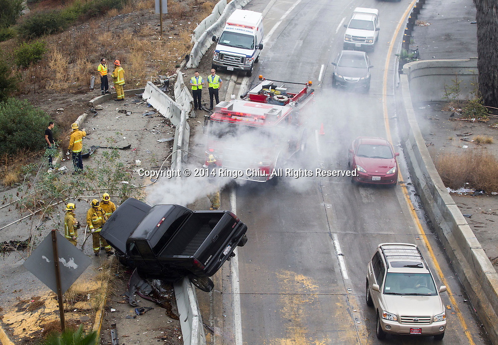Firefighters respond to a pick-up truck that crashed on the shoulder of eastbound 101 Hollywood Freeway near downtown Los Angeles, Wednesday, December. 3, 2014. Between midnight and 11 a.m. today, there were 189<br /> traffic crashes on rain-slick Los Angeles County freeways, according to the California Highway Patrol.<br />  (Photo by Ringo Chiu/PHOTOFORMULA.com)