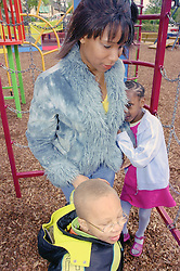 Single mother with young daughter and son in playground,