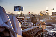 "View from behind the barricades blockading a building supplies store named ""Epicenter"" in the city of Lviv, Ukraine. Two people passing by."