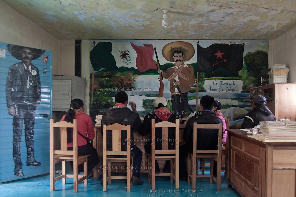 """La junta de buen gobierno en reunion, en frente la imagen emblematica de Emiliano Zapata y la escrita """"la tierra es de quien la trabaja"""".<br /> The good government junta in a reunion. In front the Emiliano Zapata portrait and the writing """"the land belongs to those who work on it"""""""