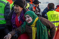 LESVOS, GREECE - FEBRUARY 09: A refugee helps Sara to get off a dinghy where she arrived with her son and grandsons after crossing the Aegean sea from the Turkish coast on February 09, 2015 in Lesvos, Greece. Photo: © Omar Havana. All Rights Are Reserved