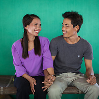 A young couple of farmers sit together and hold hands in Cambodia.