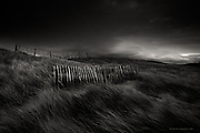 Awarded a discretionary MERIT in the 29th SUN (Shot up North) Awards for full time professional photographers<br /> <br /> Nominee in Fine Art Category / B&W Spider Awards 2017<br /> <br /> Tiny blades of light penetrated the thick armour of black clouds over the Irish Sea. Pierced into soft dunes were short lengths of delicate fencing, resolutely standing their ground in the shifting sand, but gradually becoming eroded by the relentless attack of wind and weather.
