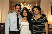Iris Garcia Costa poses for a portrait with her parents Montecristi Garcia and Eulina Costa at her fifteenth birthday party. The Quinceañera, is the traditional coming-of-age party for 15-year-old girls in Cuba, and other Spanish speaking countries. From coverage of revisit to Material World Project family in Cuba, 2001.