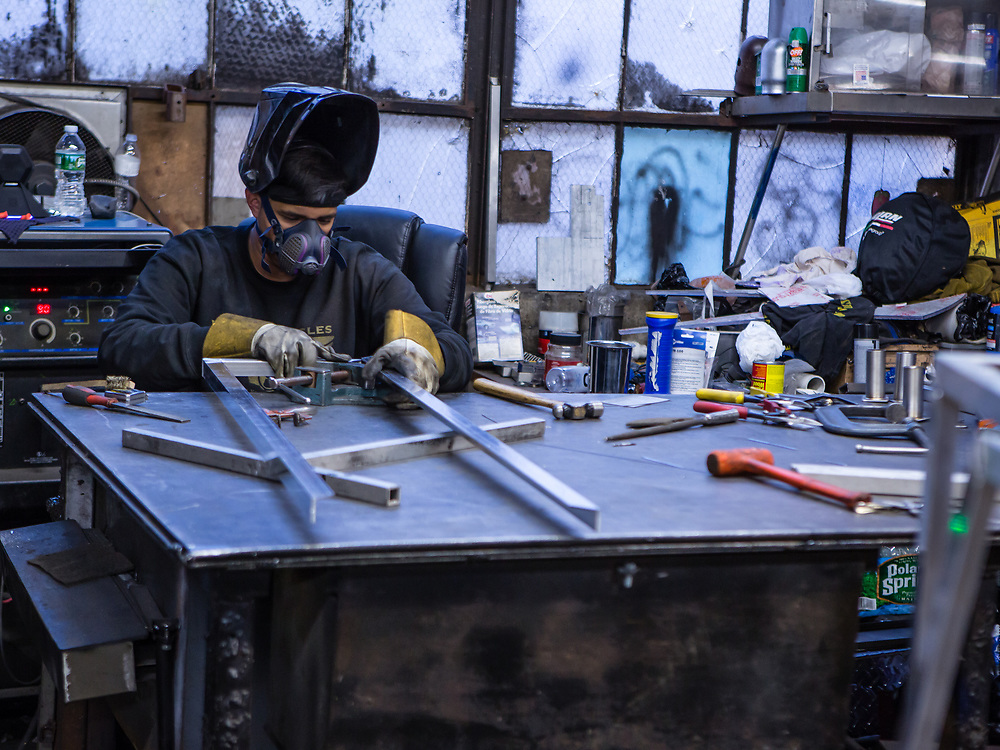 Welder Joshua Sanchez working on an aluminum frame for a food cart canopy. The carts are made of stainless steel inside and out, but the canopies are framed with aluminum to save weight.