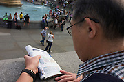 Male tourists from Asia reads a tourist map in London's Trafalgar Square.