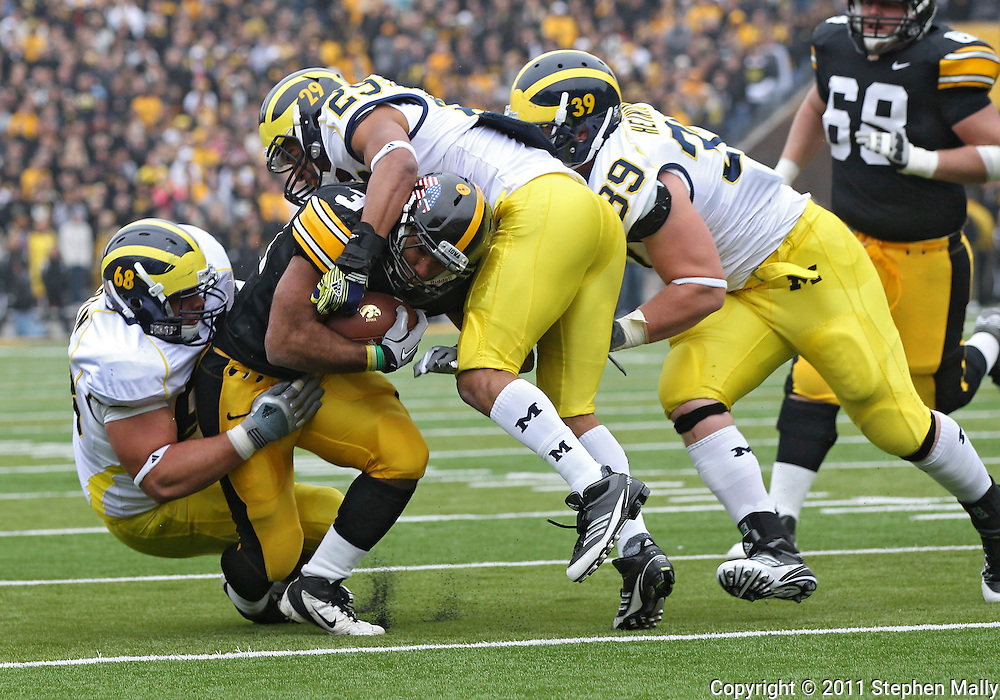 November 05, 2011: Iowa Hawkeyes running back Marcus Coker (34) is hit by Michigan Wolverines defensive tackle Mike Martin (68) and Michigan Wolverines cornerback Troy Woolfolk (29) during the first quarter of the NCAA football game between the Michigan Wolverines and the Iowa Hawkeyes at Kinnick Stadium in Iowa City, Iowa on Saturday, November 5, 2011. Iowa defeated Michigan 24-16.