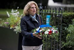 © Licensed to London News Pictures. 11/09/2021. London, UK. Members of the public place flowers at a memorial in Grosvenor Square in London on the 20th anniversary of the 9/11 terrorist attack. The attacks, which killed a total of 2,977 people, saw passenger jets seized by suicide attackers, flown into the Twin Towers of the World Trade Center in New York and the The Pentagon building. Photo credit: Ben Cawthra/LNP