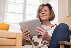 Low angle view of a senior woman sitting on chair and using a digital tablet, Munich, Bavaria, Germany