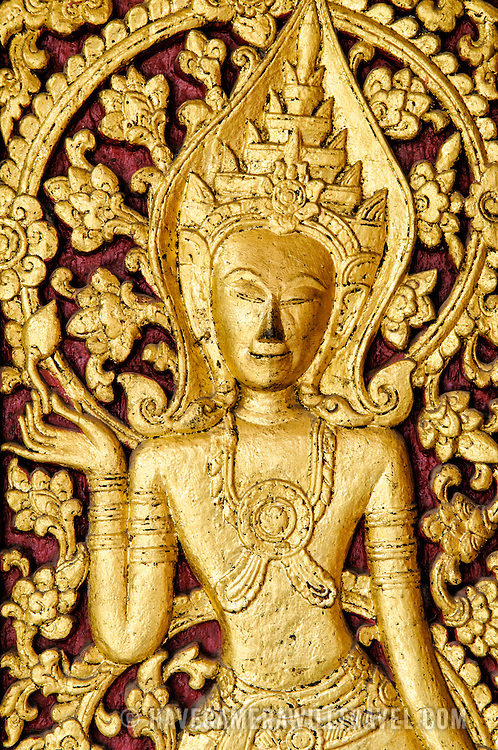 A gold figure against a dark red background on the exterior door at Wat Mai Suwannaphumaham.  Wat Mai, as it is often known, is a Buddhist temple in Luang Prabang, Laos, located near the Royal Palace Museum. It was built in the 18th century and is one of the most richly decorated Wats in Luang Prabang.