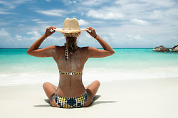 woman with straw hat sitting on the beach, Koh Lipe, Thailand