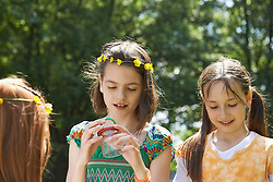 Girls examining a spider in container, Munich, Bavaria, Germany