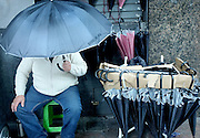 Pablo Vignali/ URUGUAY/ MONTEVIDEO/ Día de lluvia en Montevideo. Fotografías tomadas sobre la avenida 18 de Julio.<br /> En la foto: Vendedor de paraguas. Foto: Pablo Vignali / adhocFotos<br /> 20160310; día miércoles<br /> adhocFOTOS
