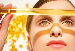 Close up of a young woman face holding a golden glass tube over her face