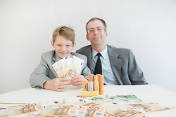 Father and son with Euro coin, paper money and coin rolls, smiling, portrait