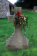 Family headstone in church graveyard decorated with holly for Christmas, Shottisham, Suffolk, England, UK