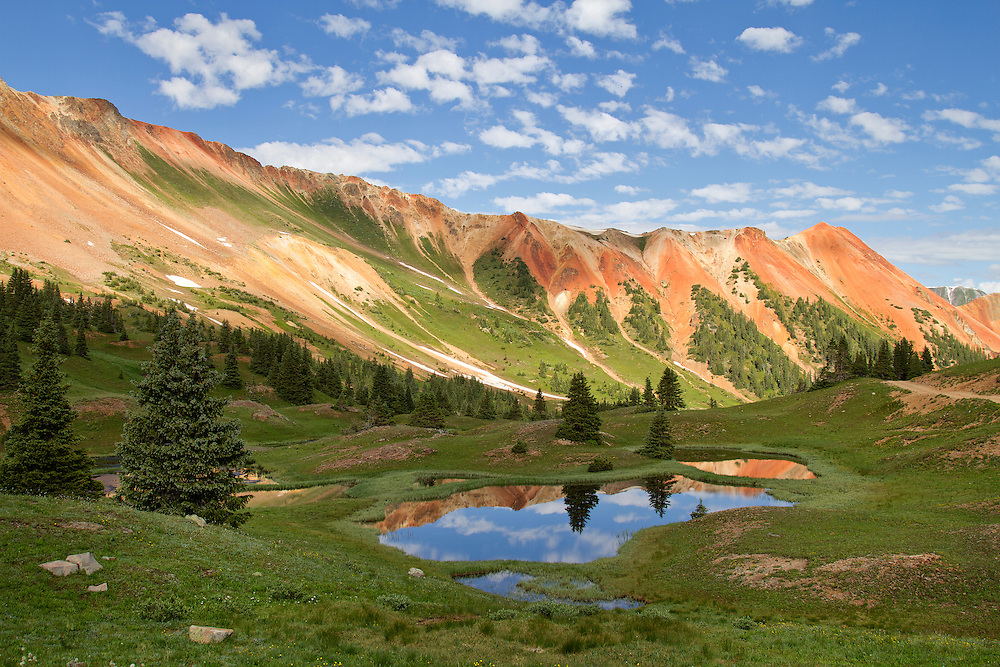 """Red Mountain is a set of three peaks in the San Juan Mountains of western Colorado in the United States, about 5 miles south of Ouray. The mountains get their name from the reddish iron ore rocks that cover the surface.<br /> <br /> 18"""" x 12""""<br /> <br /> See Pricing page for more information.<br /> <br /> Please contact me for custom sizes and print options including canvas wraps, metal prints, assorted paper options, etc. <br /> <br /> I enjoy working with buyers to help them with all their home and commercial wall art needs."""