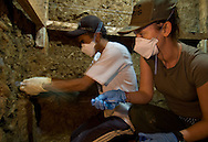 """Kira Westaway and Benjamin Tarus collect samples for dating in an excavation pit at Liang Bua cave, discovery site of the Flores """"hobbit, Homo floresiensis"""