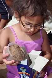 Nursery school girl pouring sand into cardboard box,