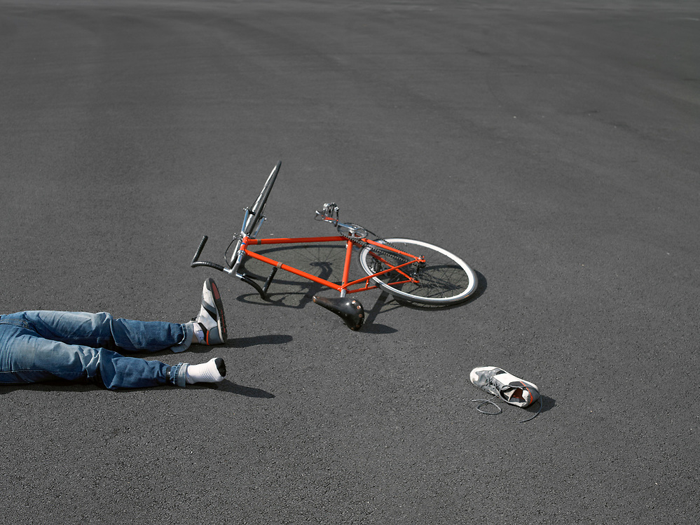 Bicycle rider crashed and fallen down on pavement.