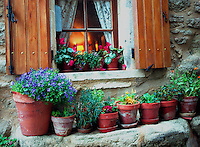Flower pots in front of window with welcoming lamplight inside, La Coste, Provence France