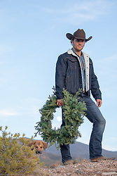 good looking cowboy holding a Christmas wreath outdoors with his puppy
