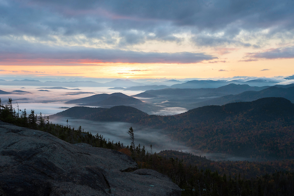 Sunrise, Ampersand Mountain, Adirondacks, NY.  It was not a good night's sleep, alone in a campsite at Saranac Lake.  Coyotes yipped and howled at sunset, and later at moonrise, a sound I love.  But the second time they woke me they were closer to my tent than I liked.  I laid there, awake now, unable to stop a marching  parade of angst that I guess we all live with.  Troubled thoughts of a too-active mind, all of them far worse than a pack of hungry dogs.  I gave up, packed up.  Walked out into a night infused with a thick fog,  following the beam of my headlamp up the mountain, determined to see the sun come up.  The summit topped just above treeline after a steep climb at the end, and I emerged onto bare rock between a sandwich of clouds.  Color graced the tops and bottoms of them, but even the light of sunrise seemed to have a hard time penetrating the gloom.  Sometimes I wonder if I bring the darkness with me, or if I'm just following it, in pursuit of things I've lost.  Another round of coyote calls, to the sunrise this time, drifted up from the denseness down there, sad and primal.  The day will move on, the slopes below will come into detail and exude autumn, and the stone will warm under my feet.  But I'll be gone, westward down the trail, descending into the shadowed side of the mountain.  Content that there's light at the top.