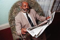 Elderly man sitting in armchair in lounge reading newspaper,