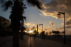 © Licensed to London News Pictures. 15/01/2021. Beirut, Lebanon. The sun sets on the Corniche in Beirut, which is near empty on the second day of an 11 day curfew (from 14 Jan to 25 Jan) in an attempt to control a rapid increase in rates of COVID-19 Coronavirus in the country. Today, Lebanon registered two record-breaking statistics, with 6154 cases of Coronavirus, and 44 deaths in the past 24 hours. Photo credit : Tom Nicholson/LNP