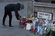 Three days after the killing of Jack Merritt, 25, and Saskia Jones, 23, by the convicted teorrorist Usman Khan at Fishmongers Hall on London Bridge, a memorial of flowers appeared at the southern Southwark end of the bridge where passers-by and commuters walk past on their way to work in the City at the opposite side of the river Thames, in the City of London, on 2nd December 2019, in London, England.