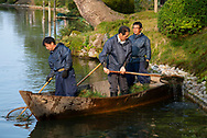 Gardeners in a small boat clearing debris from the Hisagoike Pond with nets in the Kenrokuen Garden, Kanazawa, Ishigawa, Japan
