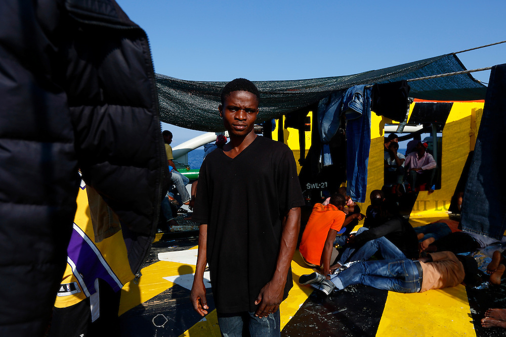A migrant stands on the deck of the Medecins san Frontiere (MSF) ship rescue Bourbon Argos somewhere between Libya and Sicily August 8, 2015.  Some 241 mostly West African migrants on the ship are expected to arrive on the Italian island of Sicily on Sunday morning, according to MSF.<br /> REUTERS/Darrin Zammit Lupi <br /> MALTA OUT. NO COMMERCIAL OR EDITORIAL SALES IN MALTA