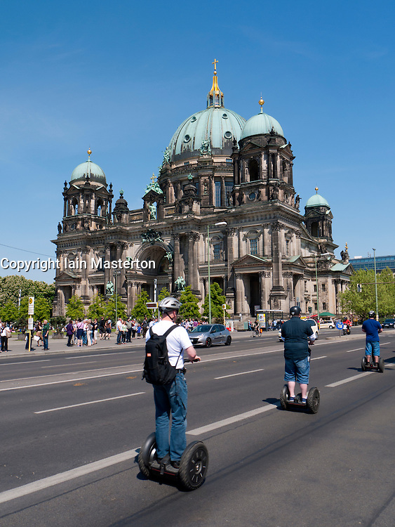 Tourists on Sedgeway tour of Berlin pass the Cathedral or Dom on Museum Island in Mitte Berlin