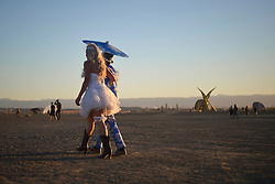 Apr 30, 2016 - Tankwa Town, Karoo Desert, South Africa - A couple dressed up as bride and groom walk among the many sculptures at this year's AfrikaBurn in the Karoo Desert, South Africa, on April 30, 2016. AfrikaBurn, the smaller cousin of Burning Man, is now in its tenth year and aims to bring together creatives from all around the world to create art, exist in a non-monetary economy, and celebrate an alternative form of living. (Credit Image: © Tobin Jones/ZUMA Wire/ZUMAPRESS.com)