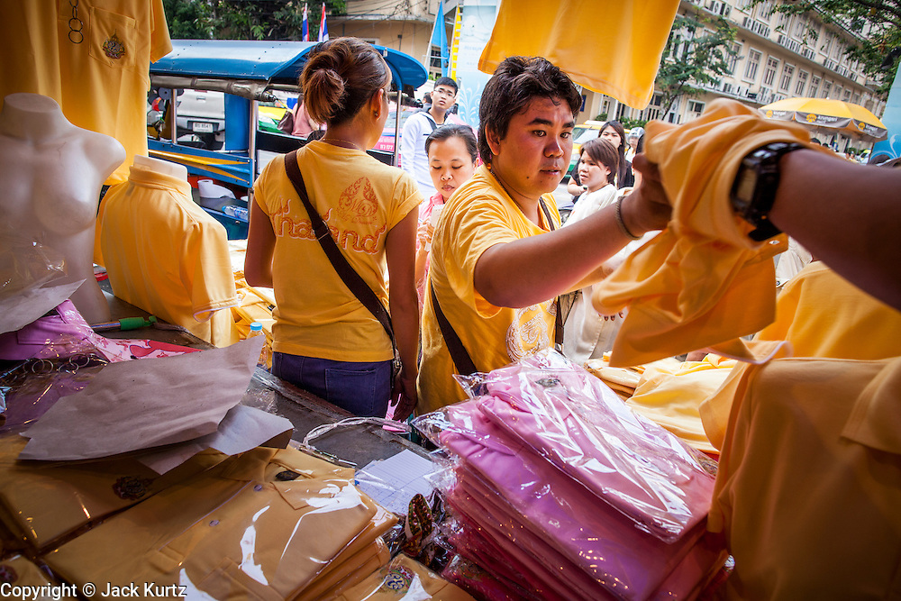 04 DECEMBER 2012 - BANGKOK, THAILAND:  People in front of Siriraj Hospital shop for yellow shirts to wear to birthday celebrations for Bhumibol Adulyadej, the King of Thailand. Yellow is the official color of the Thai King, who celebrates his 85th birthday Wednesday, Dec. 5. The King lives in Siriraj. He is expected to make a rare public appearance and address the nation from Mukkhadej balcony of the Ananta Samakhom Throne Hall in the Royal Plaza. The last time he did so was in 2006. His birthday is a public holiday in Thailand and hundreds of thousands of people are expected to jam the streets around the Royal Plaza and Grand Palace to participate in the festivities.   PHOTO BY JACK KURTZ