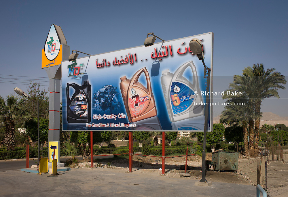 A modern billboard sign in Arabic advertising engine oils in the village of Bairat on the West Bank of Luxor, Nile Valley, Egypt.