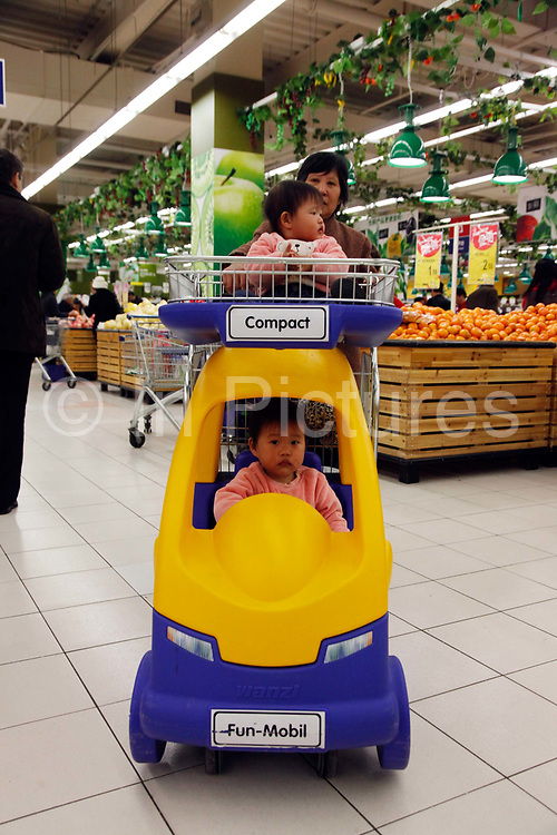 A woman pushes a shopping cart carrying a pair of twins at a supermarket in Shanghai, China on 09 December 2010.