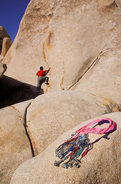 Rock climbing gear on granite rock (climber on rock wall in background), Hidden Valley, Joshua Tree National Park, California