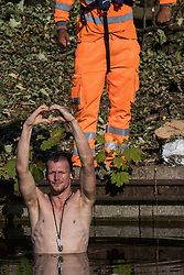 An HS2 security guard monitors an anti-HS2 activist standing in the Grand Union Canal to halt tree felling works alongside HOAC lake in connection with the HS2 high-speed rail link on 21 September 2020 in Harefield, United Kingdom. Anti-HS2 activists continue to try to prevent or delay works for the controversial £106bn HS2 high-speed rail link on environmental and cost grounds from a series of protection camps based along the route of the line between London and Birmingham.