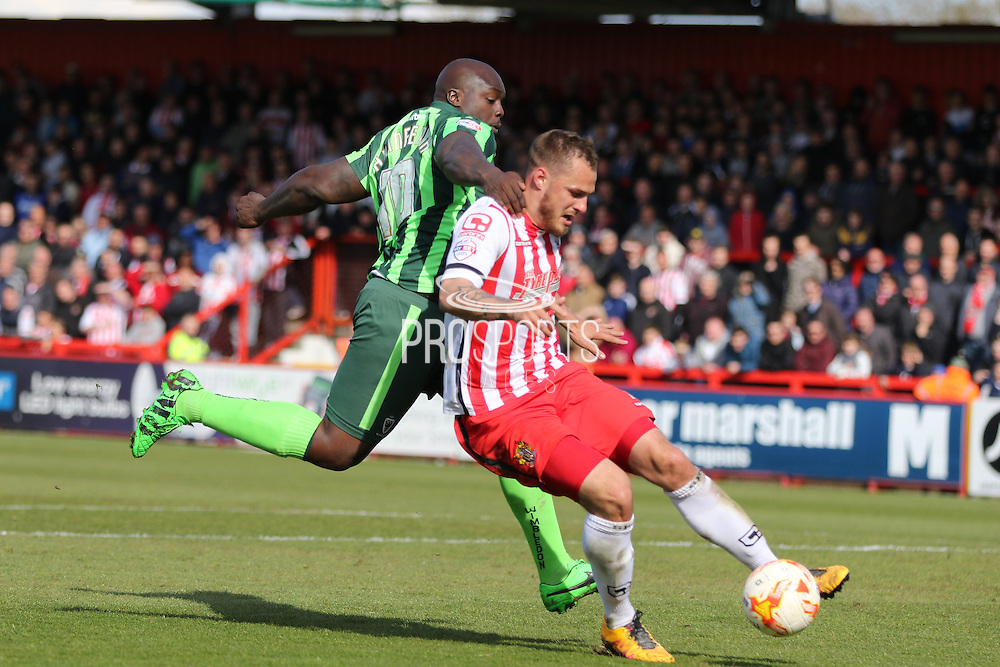 Bayo Akinfenwa forward for AFC Wimbledon (10) and Luke Wilkinson defender of Stevenage FC (2) tussle during the Sky Bet League 2 match between Stevenage and AFC Wimbledon at the Lamex Stadium, Stevenage, England on 30 April 2016. Photo by Stuart Butcher.