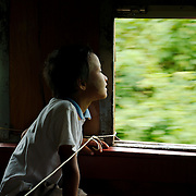 Boy looking outside near the string delimiting the area for Burmese citizens