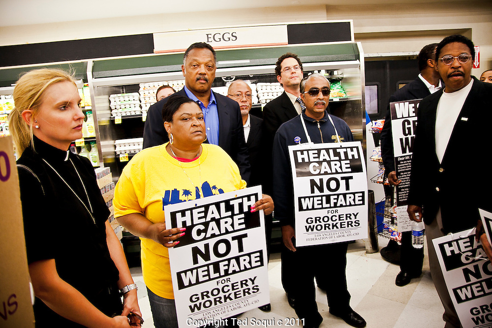 Reverend Jesse Jackson joined a group of unionized  L.A. grocery workers to help keep contract negotiation going before a Friday strike deadline..Grocery workers are being asked by management to pay more out of pocket expenses for healthcare..Jesse Jackson with local L.A.clergy walking down an isle at Ralphs Supermarket in South L.A.