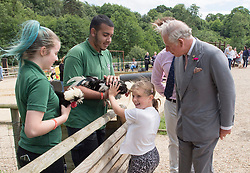 The Prince of Wales with eight year old Skye Skillen from Colchester looking at chickens during his visit to Jimmy's Farm in Ipswich where he met the trust's new President, Jimmy Doherty, and learned about the farm's education and rare breeds programme.