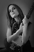 Beautiful woman in a black top with a Fender Jaguar guitar