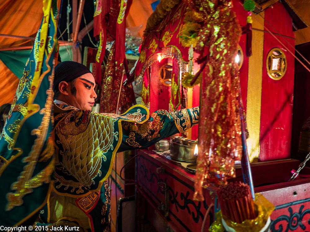 15 OCTOBER 2015 - BANGKOK, THAILAND: A Chinese opera performer prays before going on stage at the Vegetarian Festival at the Joe Sue Kung Shrine in the Talat Noi neighborhood of Bangkok. The Vegetarian Festival is celebrated throughout Thailand. It is the Thai version of the The Nine Emperor Gods Festival, a nine-day Taoist celebration beginning on the eve of 9th lunar month of the Chinese calendar. During a period of nine days, those who are participating in the festival dress all in white and abstain from eating meat, poultry, seafood, and dairy products. Vendors and proprietors of restaurants indicate that vegetarian food is for sale by putting a yellow flag out with Thai characters for meatless written on it in red. The shrine is famous for the Chinese opera it hosts during the Vegetarian Festival. The operas are free.    PHOTO BY JACK KURTZ