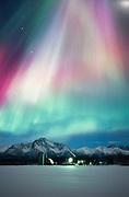 Alaska, Palmer. Aurora Borealis glow above a barn in the Matanuska Valley.