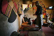 Noor Agha, about 52, at right, prays as Saboor, 6, at right, watches TV, in the house, Kabul, Afghanistan, Thursday, March, 8, 2007. Noor Agha is a renowned kite maker who made kites for the movie makers of the best-selling novel, The Kite Runner, which will be distributed by Dreamworks and Paramount Vantage in Nov. this year. Noor Agha's wives, using their special glue, help him produce enough kites to please the clients' needs. Some of his children can also make their own kites with plastic bags and bamboo sticks. As the Afghan New Year's Day (Nawruz) approaching on March 21, the finger tips of Noor Agha's family got busier for mass production.